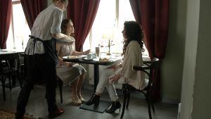 Pia-Maria Lehtola och Tiina Helminen talar om danskt mode på ett café.