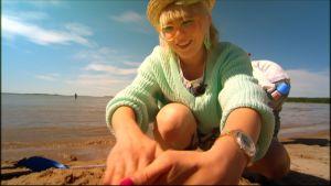 Laila tekee hiekkalinnan Yyterissä.