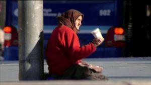 äldre romsk kvinna tigger mitt i trafiken med pappmugg
