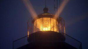Isokarin majakan valo loistaa pimeässä.