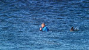 Surfaren Mick Fanning med en olycksbådande ryggfena bakom ryggen.