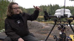 Mies esittelee multikopteria, joka kantaa elokuvakameraa.
