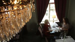 sofie asplund och pia-maria lehtola sitter på café under en kristallkrona
