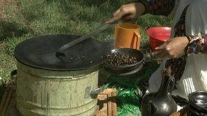 Etiopialainen nainen paahtaa kahvipapuja