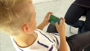 Poika pelaa mobiilipeliä