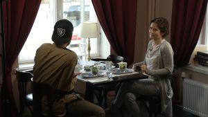 Rolf Ekroth samtalr med Pia-Maria Lehtola på ett café