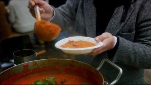 Hen häller upp soppa i en tallrik