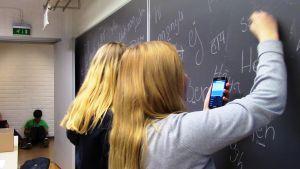 Tytöt kirjoittavat tervehdyksiä tauluun