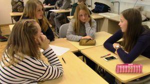 Tytöt istuvat ryhmässä luokassa