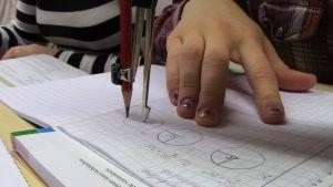 Tyttö piirtää harpilla ympyrää