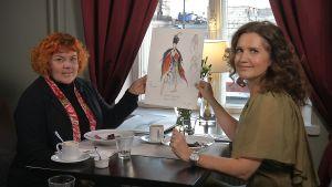 Erika Turunen tittar på en skiss av en scendräkt för Den lilla sjöjungfrun tillsammans med Pia-Maria Lehtola