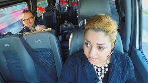Nainen ajaa taksia, mies istuu takapenkillä.