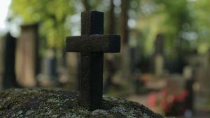 Metalliristi hautamuistomerkin päällä Hietaniemen hautausmaalla.