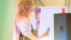 Ljushårig flicka uppför en egen låt med svart gitarr i handen.