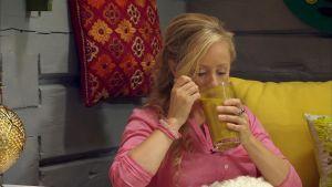 En kvinna som dricker en varm dryck med gurkmeja och mjölk.