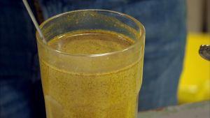 En gulbrund dryck kallad guldmjölk i ett glas