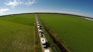 Asuntoautoja jonossa Suviseuroihin pienellä peltotiellä.
