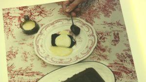en chokladkaka med vanilsås på en gammaldags porslinstallrik