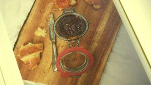en croissant och en marmeladburl på en skärbräda