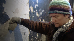 Historioitsija Teemu Keskisarja nojaa kädellä sellin seinään.