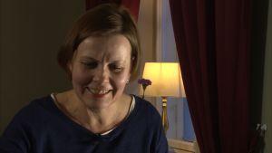 Kirsi Pullinen ler på ett café i Helsingfors.