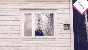 Pitsiverhot puutalon ikkunassa.