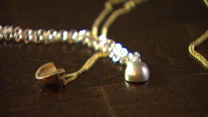 En silver- och en guldfärgad hästhov i ett smycke.