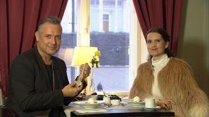 Marko Björs håller upp ett egendesignat silversmycke brevsi Pia-Maria Lehtola.
