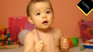 Lapsi helmet kaulassa ilman paitaa.