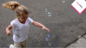 Tyttö juoksee saippuakuplien perässä.