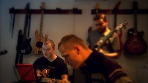 Tre killar spelar gitarr