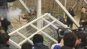 Flyktingar river ner del av gränsstängsel mellan Grekland och Makedonien.