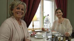 Liisa Skurnik och Pia-Maria Lehtola sitter på ett café.