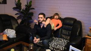 Seval Bitic sitter med sin dotter Latifa på axlarna
