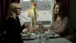 Carolina Forss och Pia-Maria Lehtola sitter på ett café och diskuterar mode.