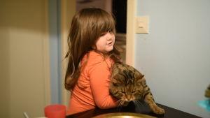 Sevals dotter Latifa lyfter en katt