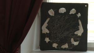 Ett konstverk med svart botten och vita porslinsblommor och mårdhundständer.