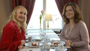 Laura Paloheimo och Pia-Maria Lehtola sitter på ett café.