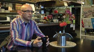 Frej Renvall sitter på café med en kaffekopp i handen