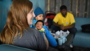 Lotten Walker med sin nyfödda bebi och familjen i bakgrunden