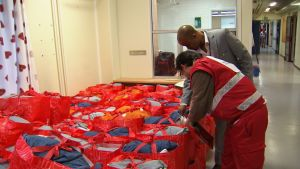 Röda Korsets anställda och frivilliga granskar välkomstväska