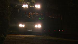 en buss med asylsökande anländer till Patis utanför Åbo, nattbild
