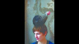 Marije Vogelzang har en svart höna på sitt huvud.