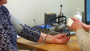 Läkare undersöker blodtryck på Folkhälsans läkarstation i Karis.