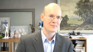 Aku Sorainen driver en av de största baltiska advokatbyråerna. I bakgrunden ett foto på hans döttrar.