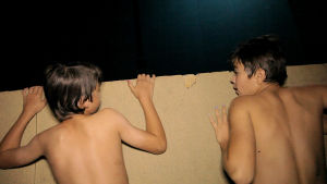 Två pojkar lutar sig mot en pappskiva på natten.