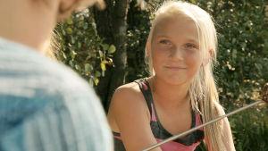 Blond flicka ler.
