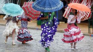 Flamencoasuiset naiset rientävät sateenvarjojen alla feria-alueella Sevillassa.
