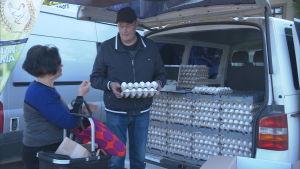 Kvinna köper ägg av man som står vid en bil packad med ägg