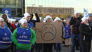 Demonstranter samlas på medborgartorget för att protestera mot regeringens planer för äldreomsorgen.